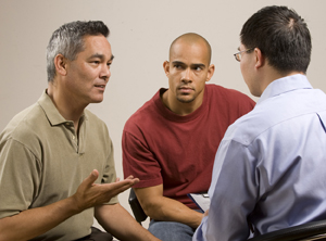 Two men in group discussion with healthcare provider.