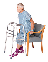 Woman lowering herself into chair keeping operated leg slightly out in front.