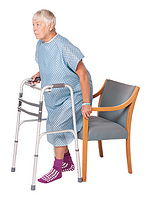Woman with a walker backing up into chair, one hand on walker and one on the arm of the chair. The chair is touching the back of her legs.