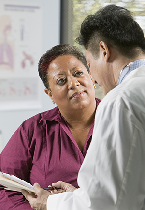 Woman talking to healthcare provider in exam room.