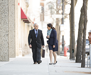 Man and woman in business attire walking together on city street