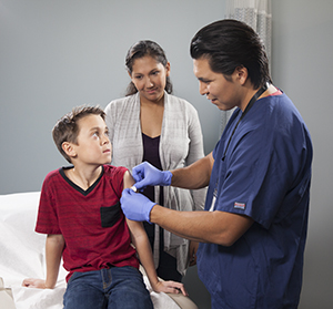 Healthcare provider giving boy injection in arm while woman looks on.
