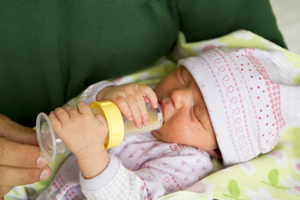 Newborn baby drinking from a bottle
