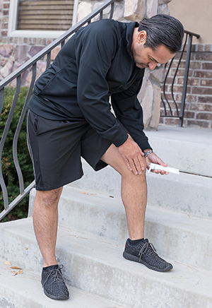 Man putting ointment on knee before exercise.