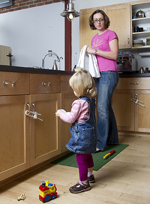 Woman watching toddler girl play in kitchen. Safety latches are on cabinets.