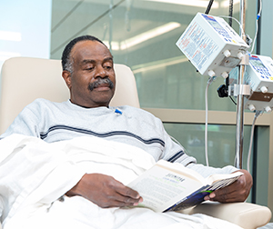 Man sitting in chair having infusion treatment.