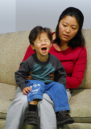 Mother comforts little boy holding his breath.