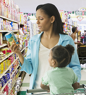 Woman at the grocery store with young child, reading a nutrition label