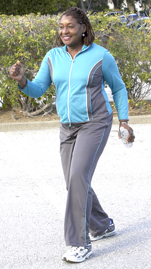 Woman in comfortable clothes walking outside carrying bottle of water.