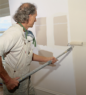 Man painting with long-handled paint roller.