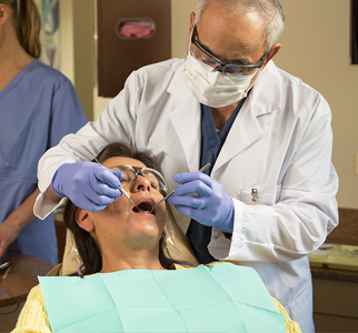 Dentist wearing face mask, working on woman's teeth