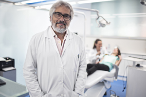 Male dentist standing and smiling in front of an exam chair.