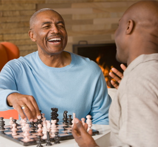 Two older men laughing while they play chess